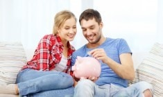 smiling couple with piggybank sitting on sofa